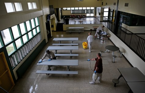 People clean and spray a room with picnic tables and seats.