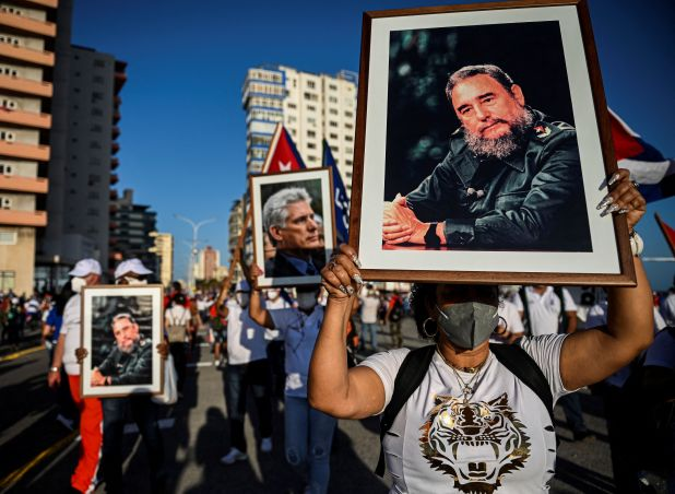 Marchers on street hold pictures of Cuban leaders