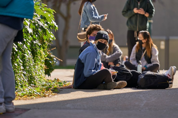 Students sit on the ground wearing face masks.
