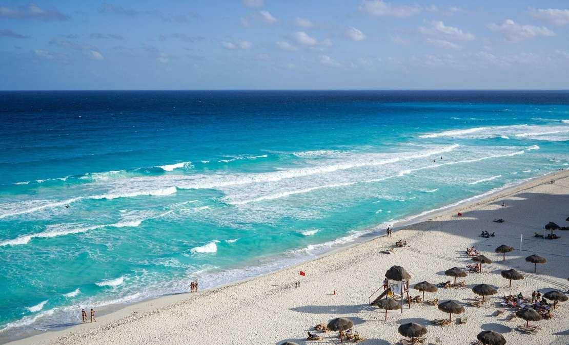 A beach and blue sea with umbrellas