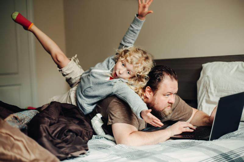 A father works at a laptop as his daughter jumps on his back
