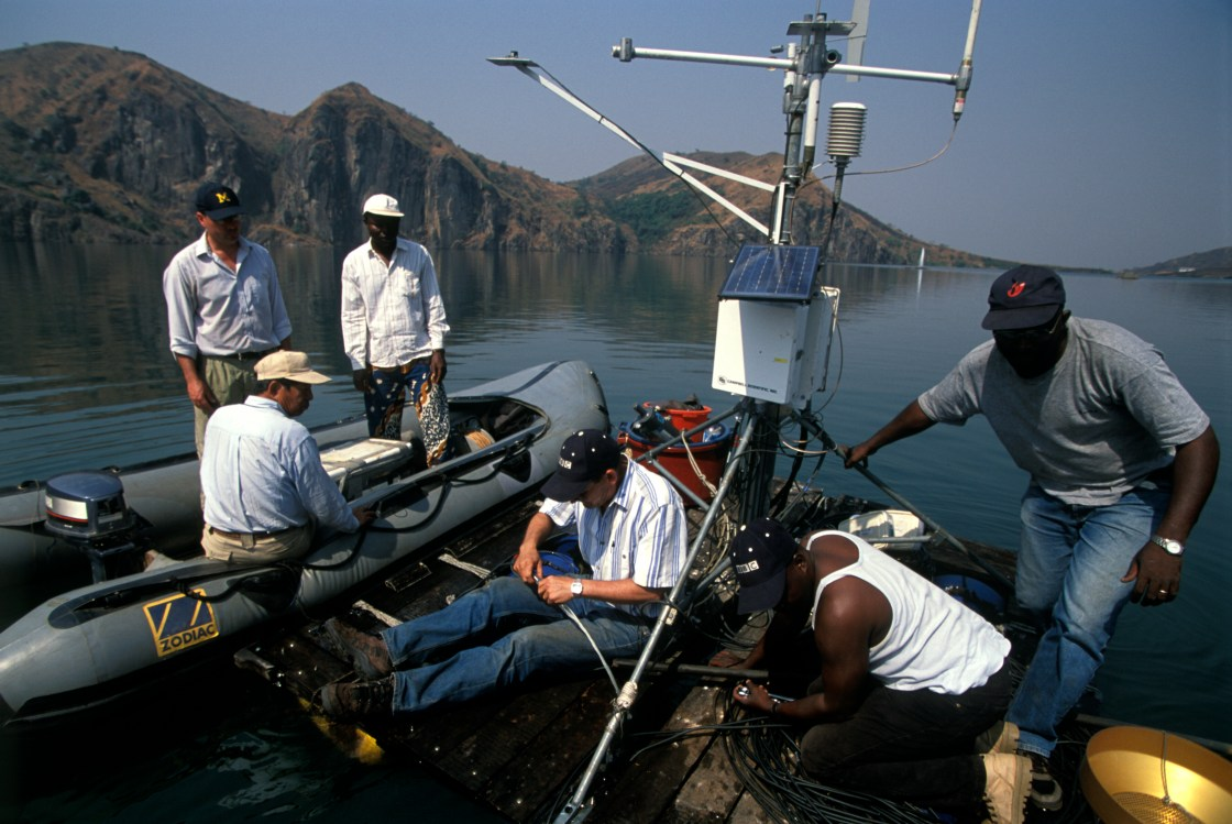 people on small boat and raft setting up scientific equipment