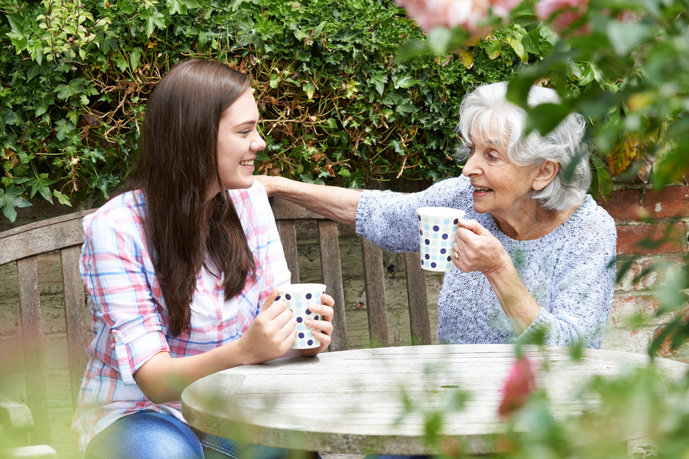 A teenager having a cup of tea with her grandmother