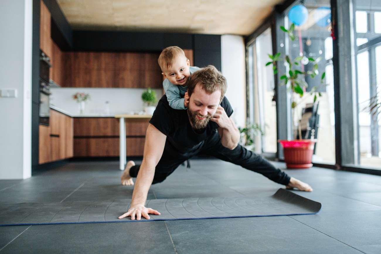Un uomo fa un push-up con un bambino sulla schiena.