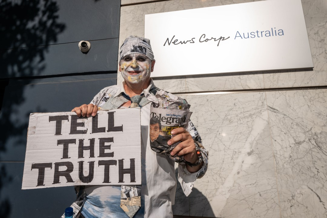 man holding sign reading 'Tell the Truth'