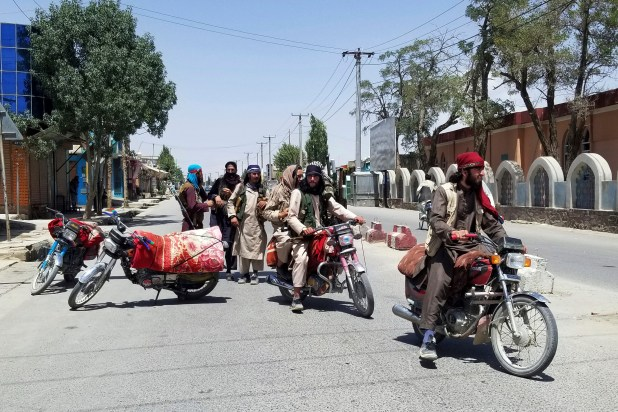 Armed men on motorcycles ride down a street
