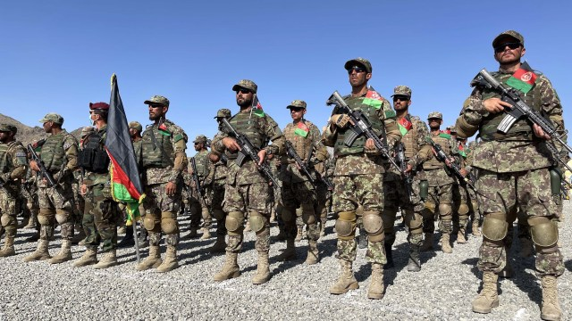 A group of people in camouflage uniforms carry rifles while standing in a formation behind the Afghan flag.