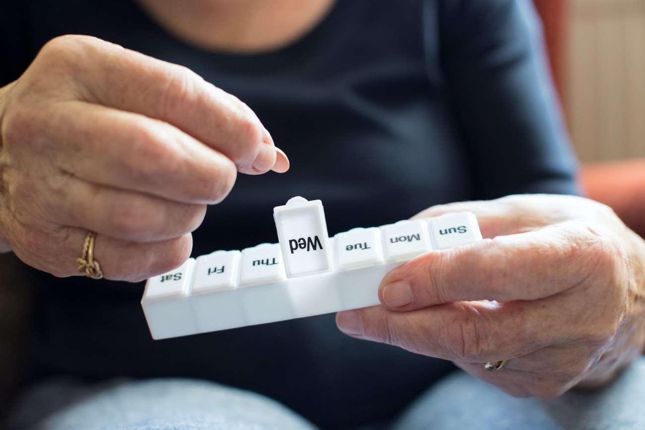 Una persona che apre una scatola di pillole.