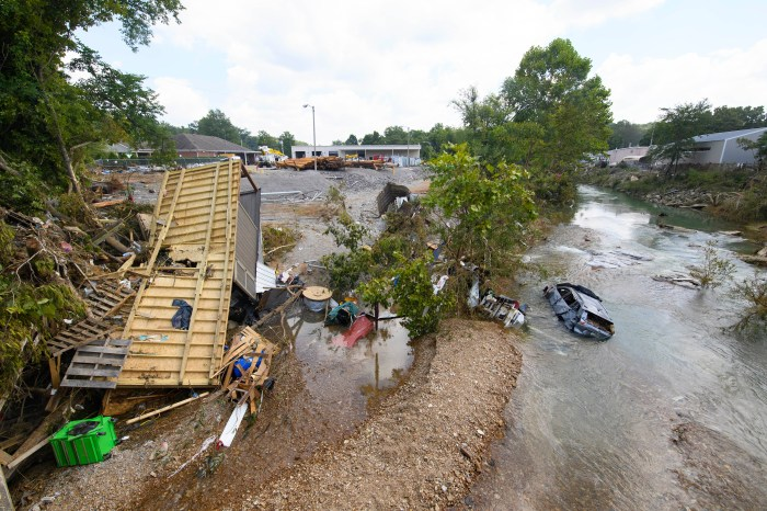 An overturned trailer and flooded car were washed into a creek by flash flooding during heavy rainfall in Tennessee.