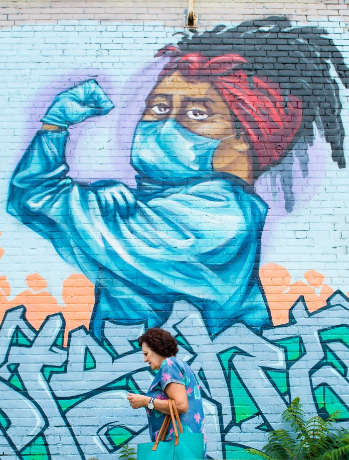 A woman in protective equipment walks near the street mural of a health care worker, flexing her biceps