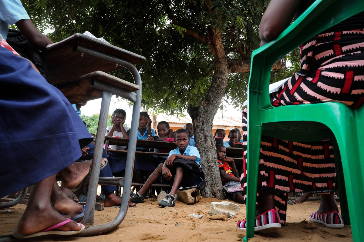 Children attend a class sitting on the ground under a tree.