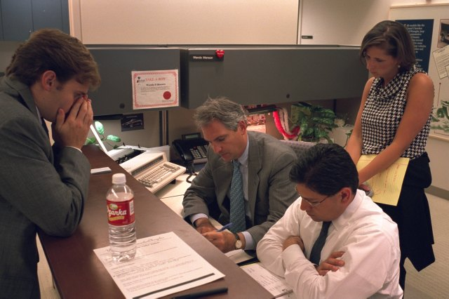 Four people working in an office together.