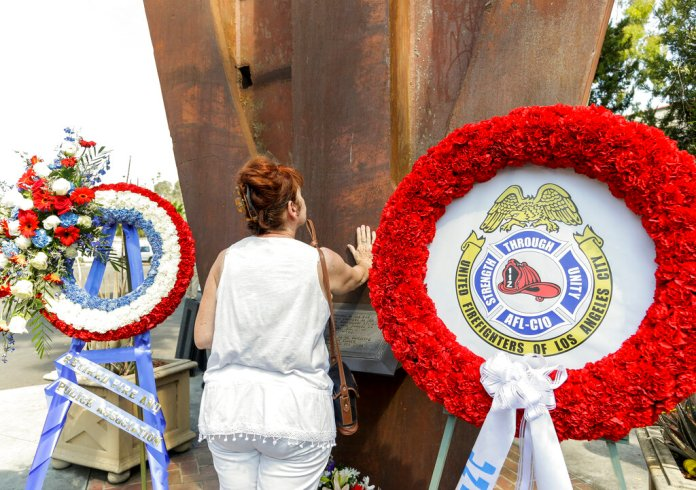 Maria Antonia Fernandez-Lopez touches an original steel beam from one of the twin towers of the World Trade Center to commemorate the 14th anniversary of 9/11 at the Frank Hotchkin Memorial Training Center in Los Angeles.
