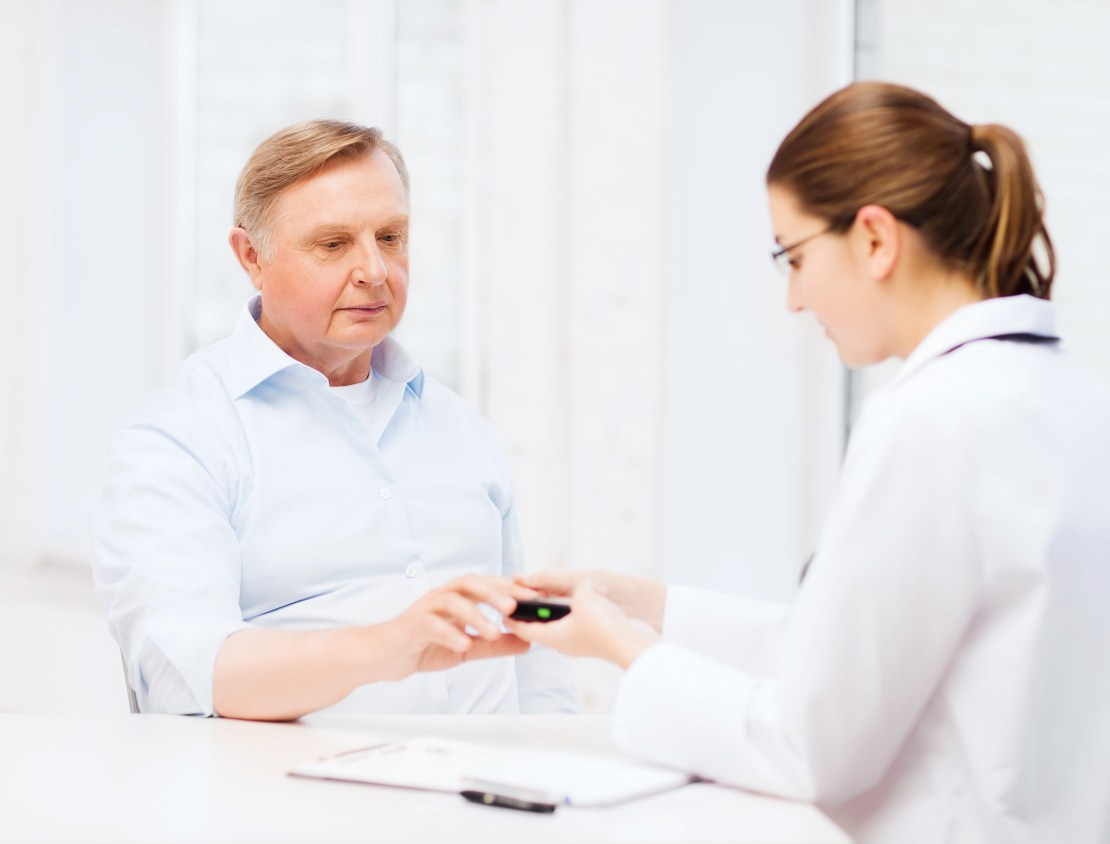 Female doctor measuring an elderly man's blood sugar levels.