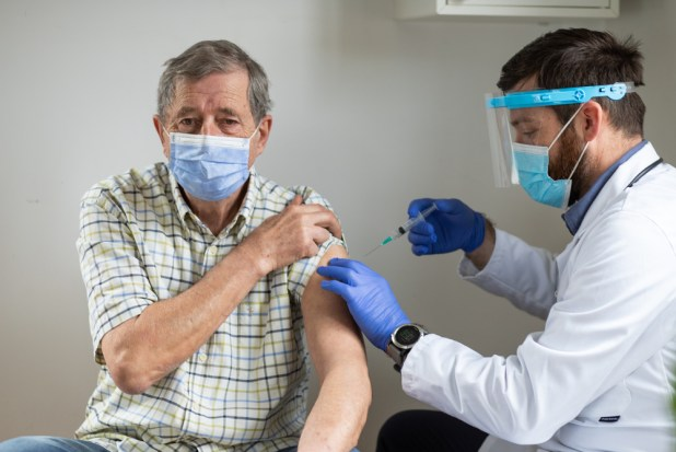 An elderly man being vaccinated against COVID-19
