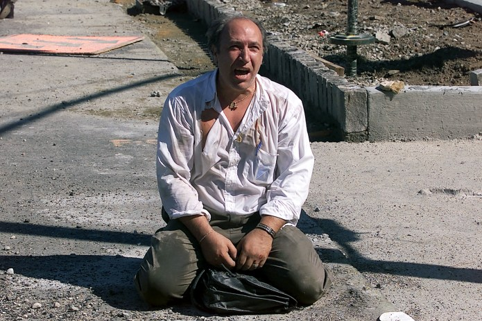 On 9/11, shortly after the terrorist attack in New York City, a distraught survivor sits outside the World Trade Center.