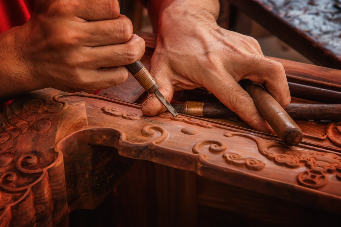 A woodworker chisels patterns into red mahogany.