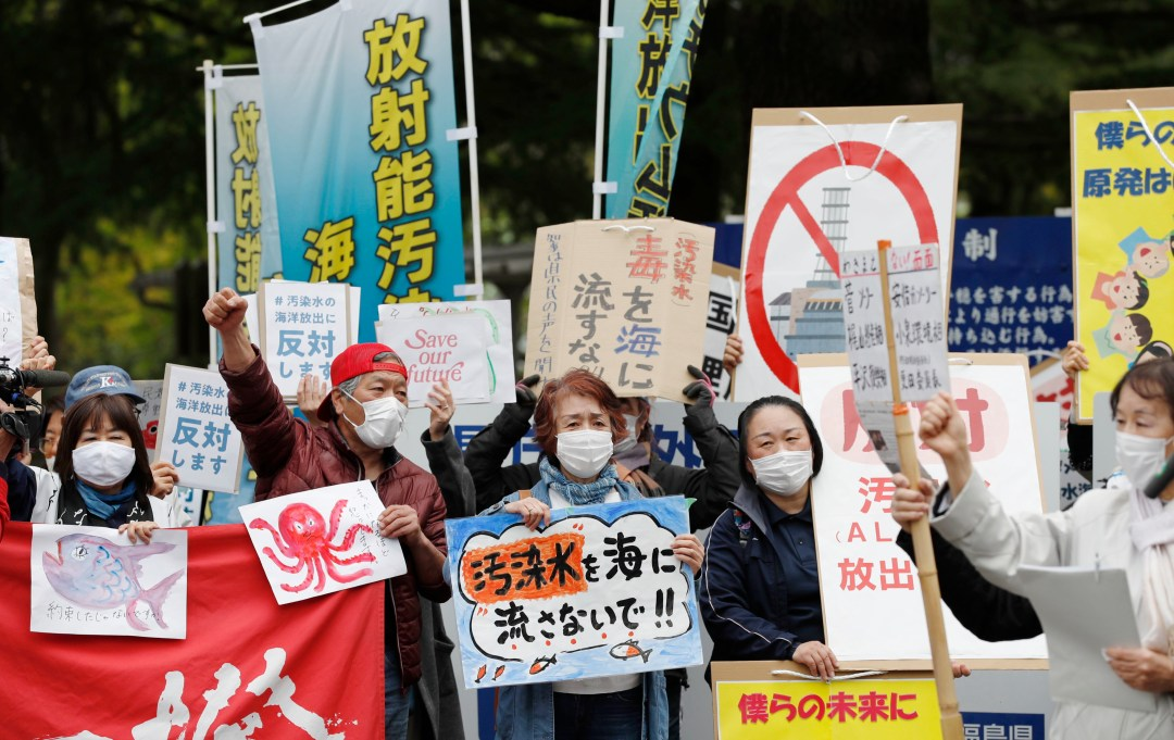 people wearing masks hold signs
