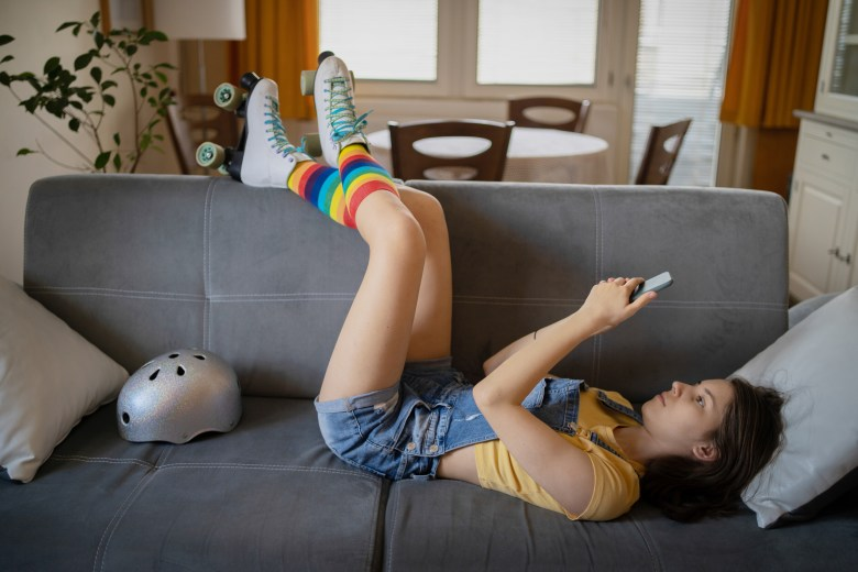 Person lying down with rainbow sock-clad legs resting on the back of a sofa.