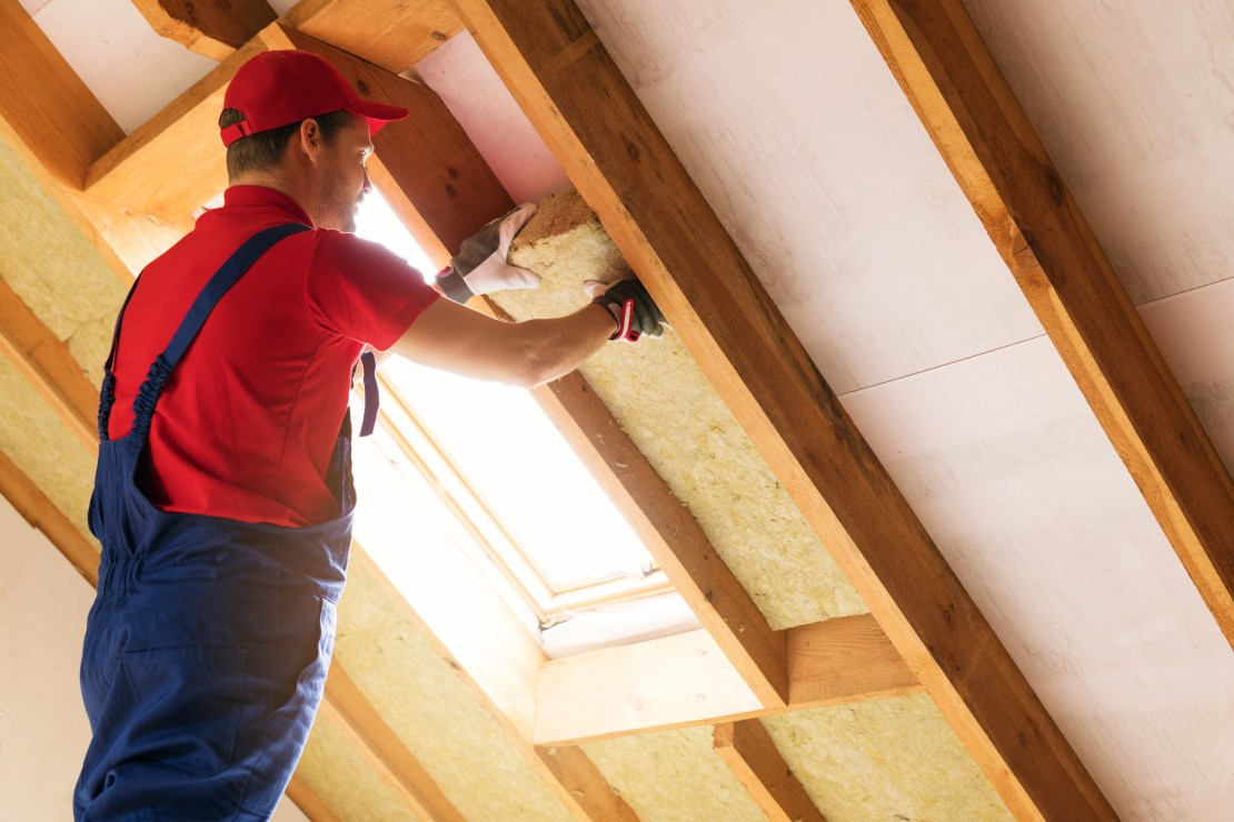 A worker in blue overalls fits wool insulation between attic roof beams.