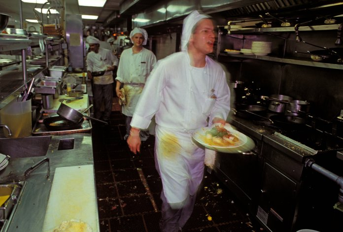 A sweaty chef walked through the rows of ovens carrying plates.When the photo was taken, the chef was slightly blurred, capturing the frantic rhythm of the kitchen