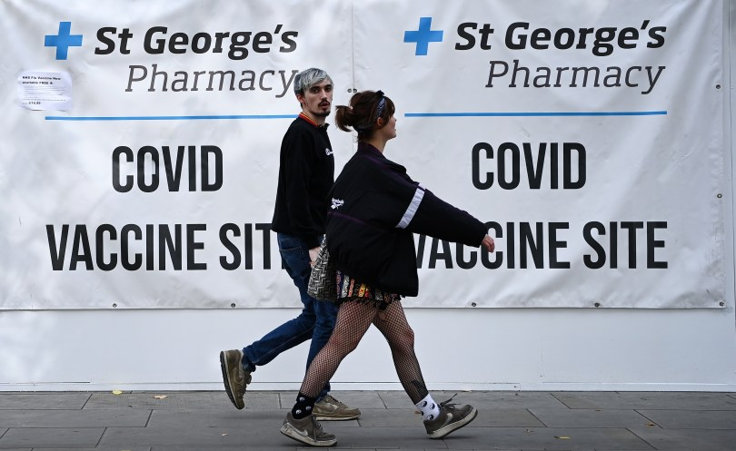 Two young people leaving a COVID-19 vaccine centre