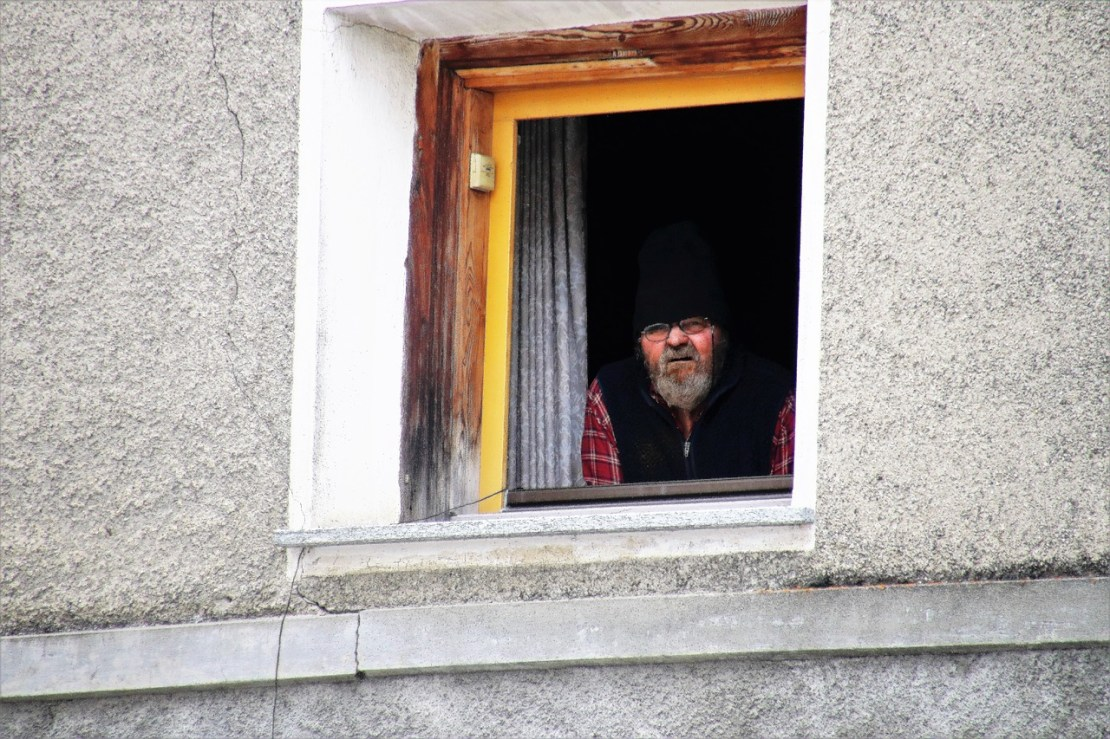 A warmly dressed person looks out of a window