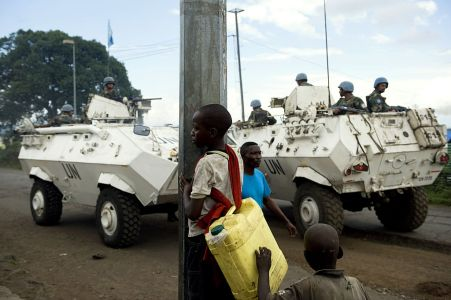 Armoured UN vehicles in the road, men wearing blue helmets on board, with some people in the foreground