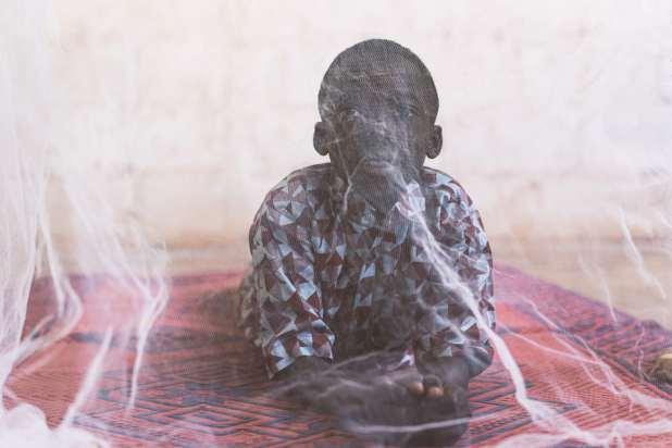 African child under mosquito net