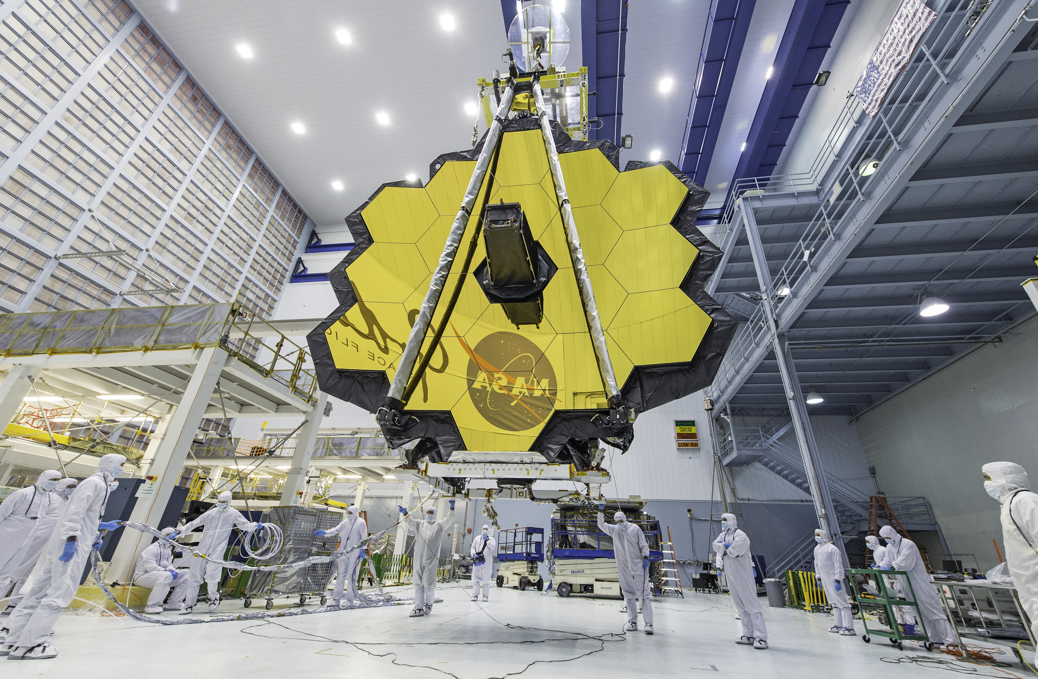 A large golden colored disc with a sensor in the middle and scientists standing below.