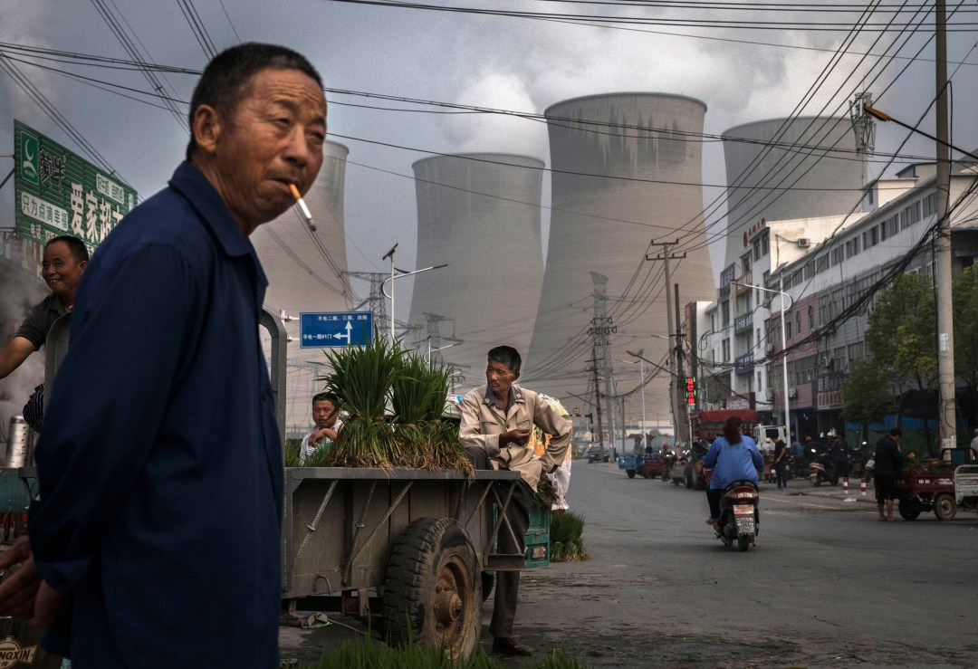 What is COP26? Here's how global climate negotiations work A man stands in a street market smoking, with cooling towers for a power plant behind him.