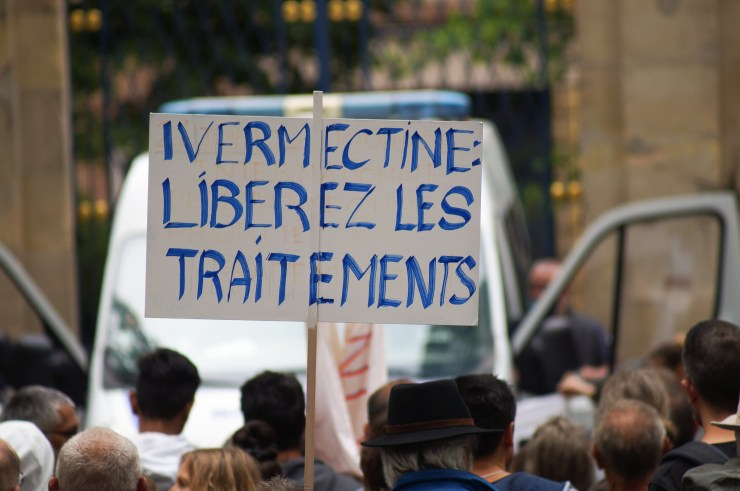 A french protester holding a placard that says 'Ivermectin: release the treatments'