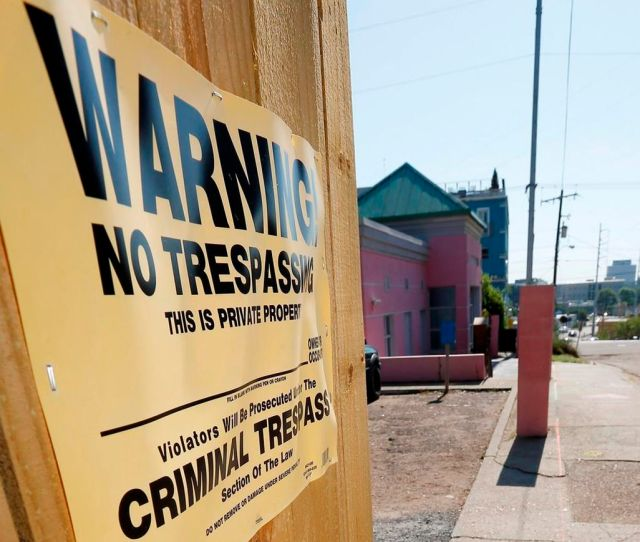 A No Trespassing Sign Is Posted Along The Fencing Protecting The Parking Lot Of