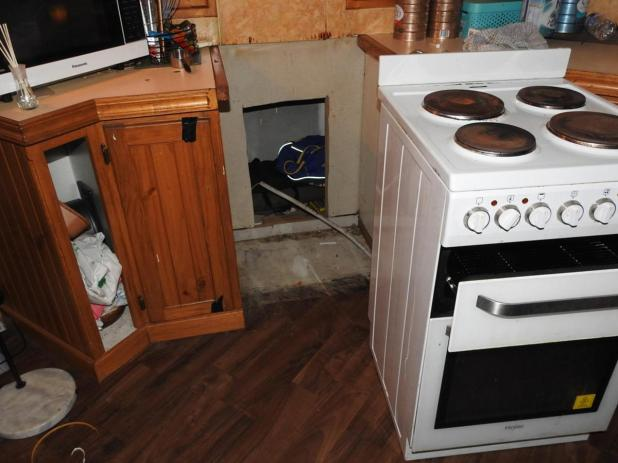 Concealed storage space behind the stove.