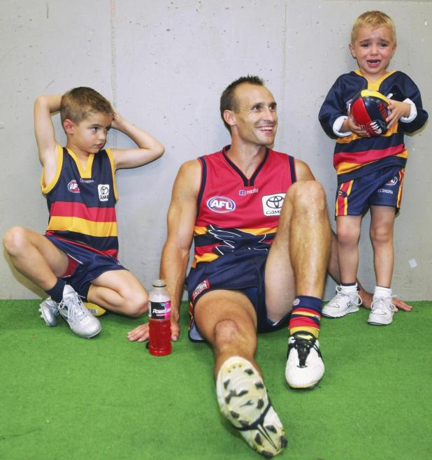 Tyson Edwards sits with his children Jackson (delisted by the Crows in 2018) and Luke.