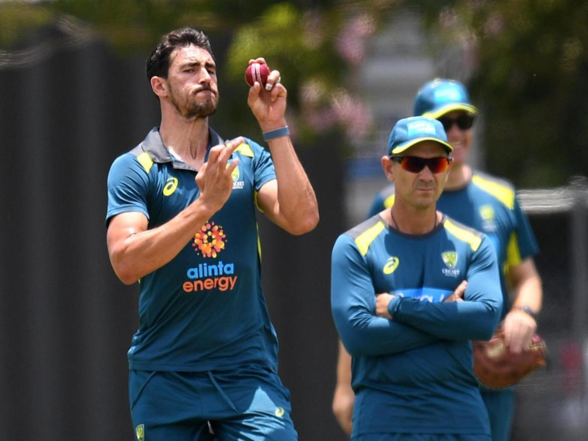 Mitchell Starc (left), watched by coach Justin Langer, bowls during the Australian Men's cricket team training.