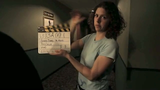 Woman holds a film clapboard in a movie theater hallway