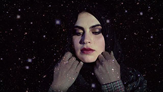 Woman pulling a hijab over her hair in front of a starry night sky