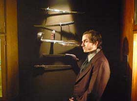 Nathan Bexton standing in front of a wall of weapons