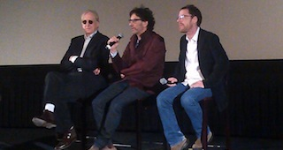 T-Bone Burnett, Joel Coen and Ethan Coen sitting on movie theater stage