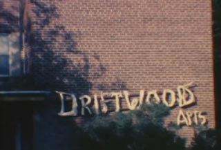 Brick apartment building with the words Driftwood Apts hanging on the outside