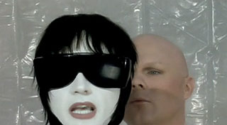 Bald man observes singing mannequin wearing sunglasses