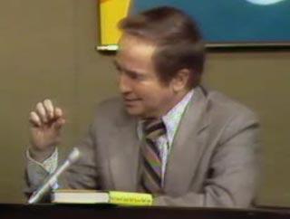 Talk show host Joe Franklin sits behind his desk on air
