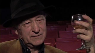 Jonas Mekas drinking a glass of wine while being interviewed