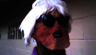 Man wearing sunglasses, a felt mask and an Andy Warhol silver wig