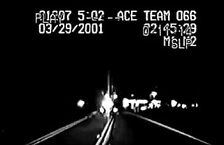 Grainy black and white footage of a police officer's dashboard camera