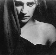 Film still from Lot in Sodom featuring a woman standing behind a curtain
