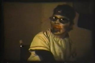 Film still from They Eat Scum by Nick Zedd featuring a man sitting in a high chair like a baby