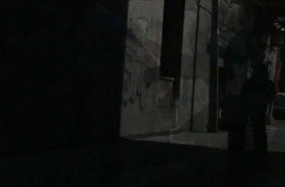 Shadow of a boy playing basketball in a dark alley