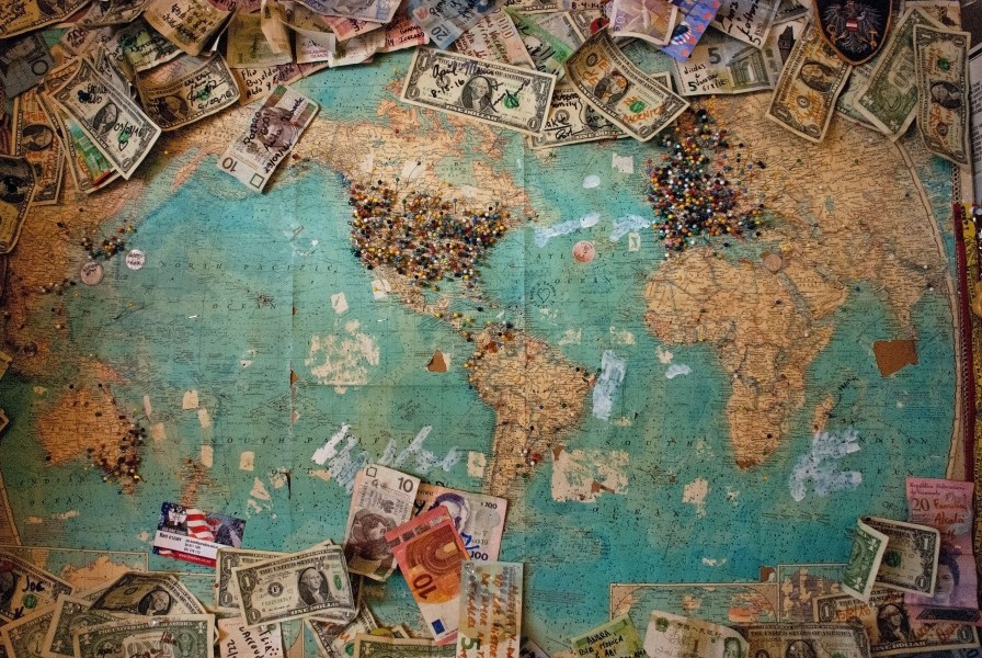 Global visitors photo by Christine Roy   agent illustrateur  on Unsplash Various currency bills pinned to a large world map with colorful pins in  various locations